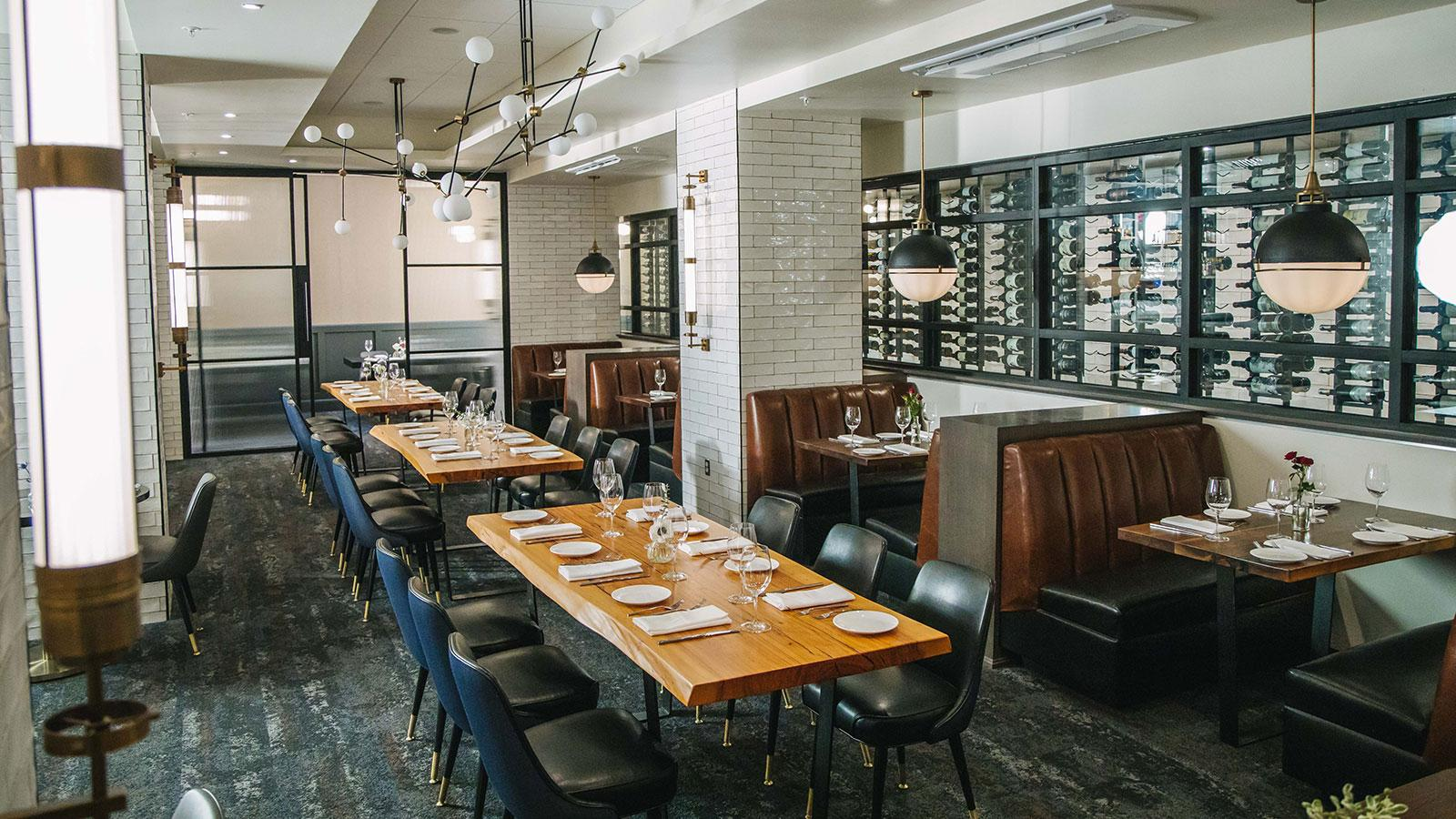 Tables in front of a display wall of wine at Wicked Butcher