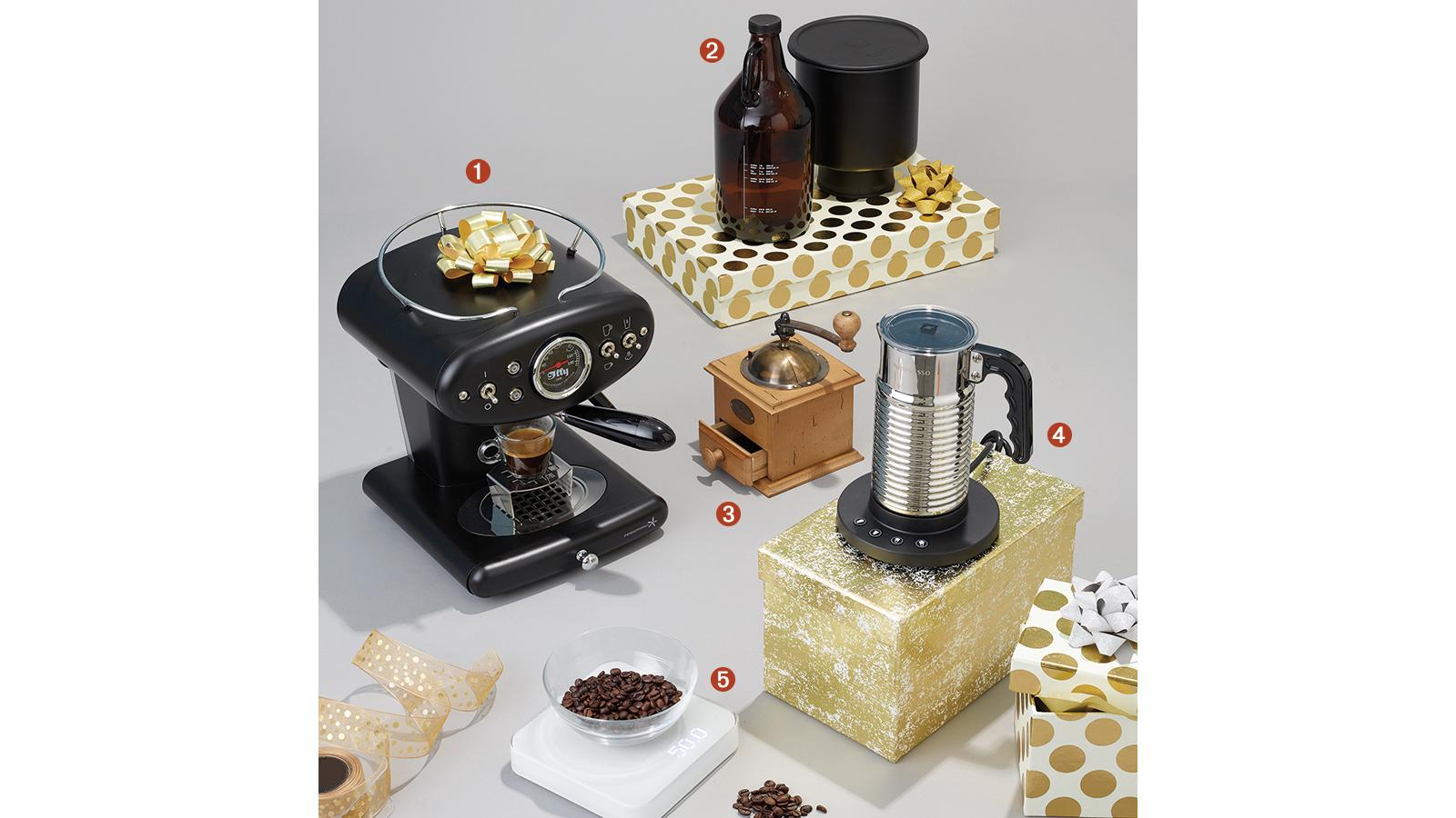 Clockwise from the left: Illy's X1 Iperespresso Anniversary 1935 Machine wwith a bow on top, Espro's Cold Brew CB1 Coffee Kit atop a gold polka dot box, Peugeot's antique coffee mill, Nespresso's Aeroccino4 milk frother standing on a gold marbled box and Acaia's Pearl coffee scale.